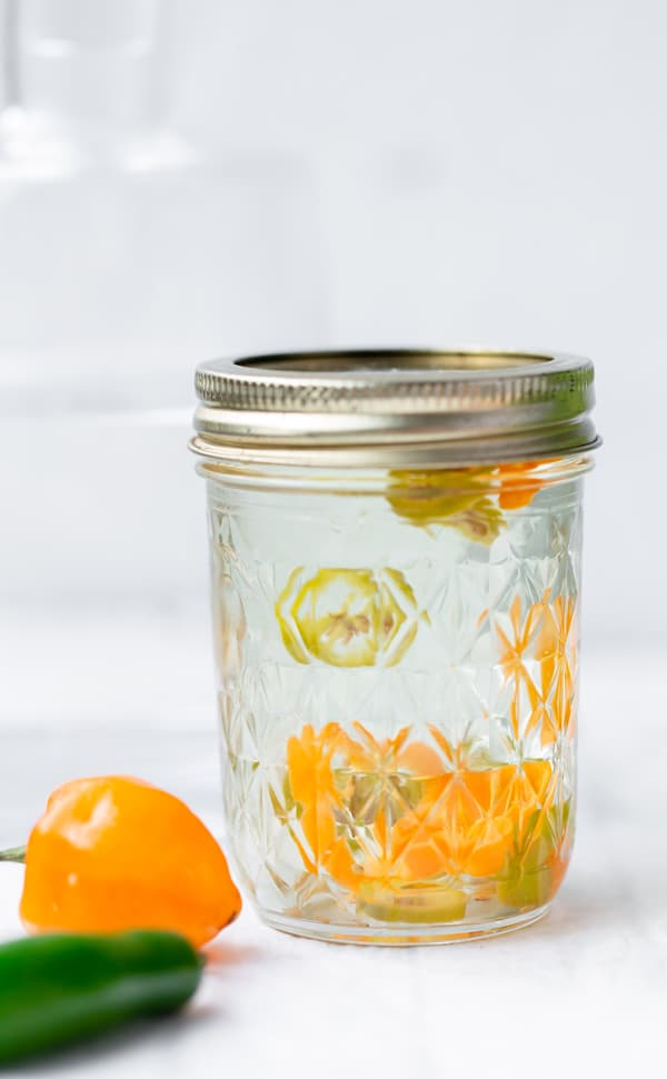 Habanero Infused Tequila adds the perfect little spicy punch to all your tequila cocktails! infused tequila | tequila | how to infuse tequila | how to infuse tequila with habanero | tequila infused with habanero jalapeno | mango habanero margarita