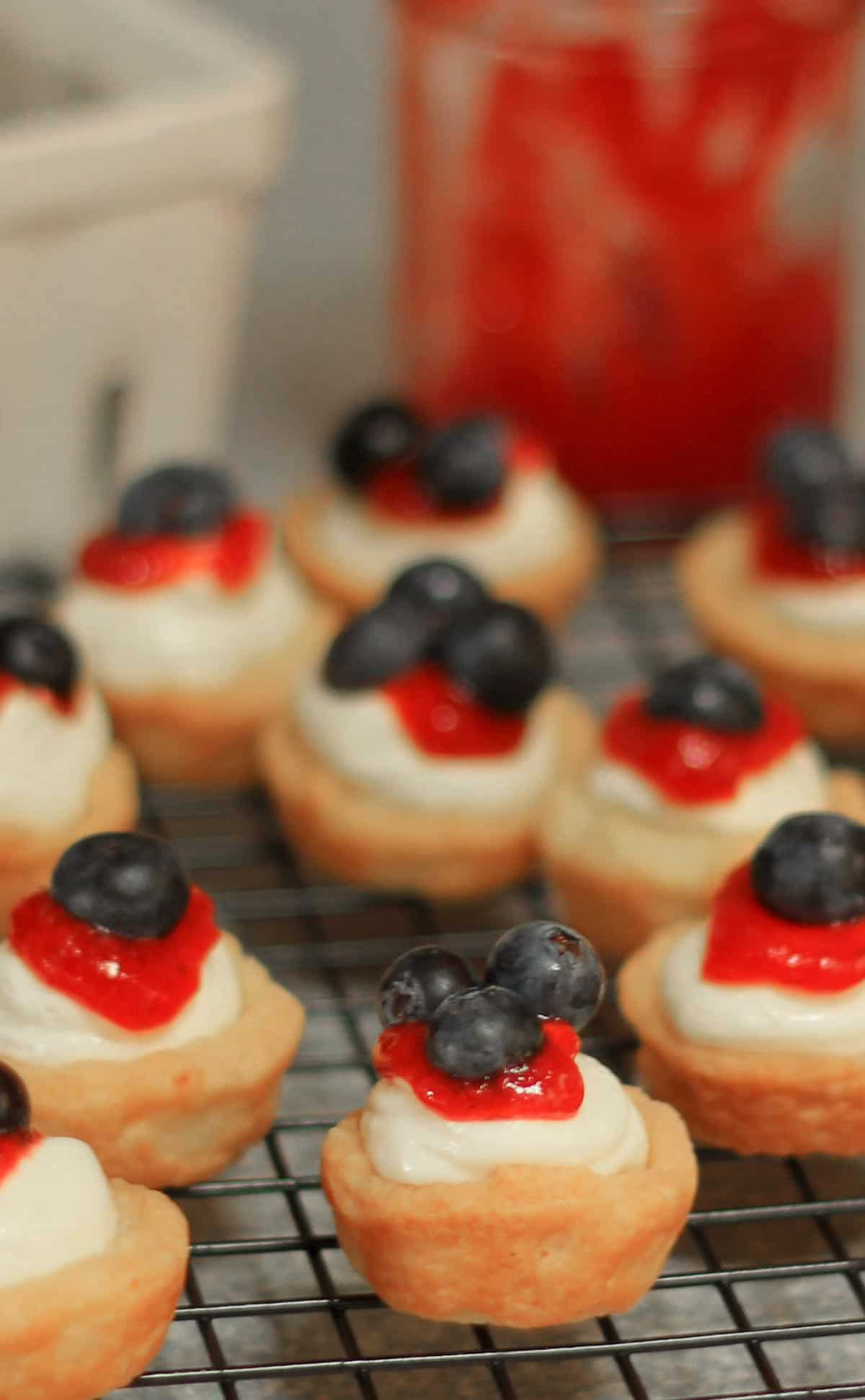 Mini Red White and Blue Lemon Cheesecake Tarts are tender homemade lemon tart shells filled with no bake lemon cheesecake filling then finished with a topping of sweet jam and berries. no bake cheesecake tarts | lemon cheesecake recipe | fruit tarts