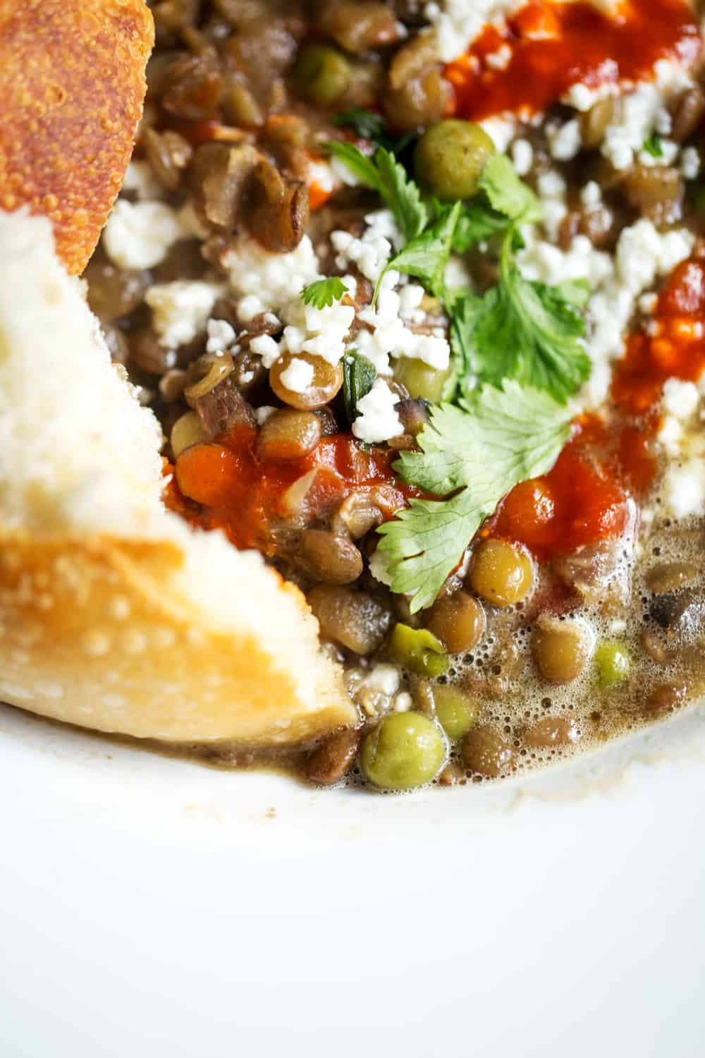 close up of green lentil stew with fresh herbs and sourdough bread