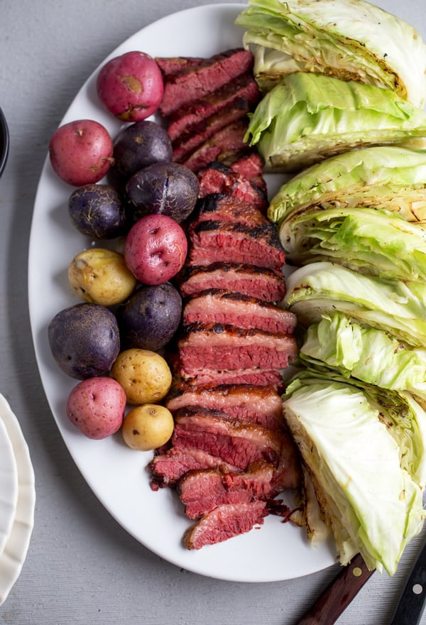 Baked Corned Beef and Cabbage braised until tender in the oven and served with tender but fresh blistered cabbage and tri color petite potatoes
