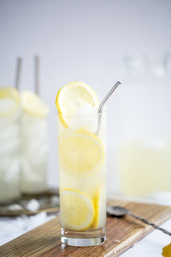 party pitcher coconut lemon sour cocktail for a crowd with fresh lemon slices