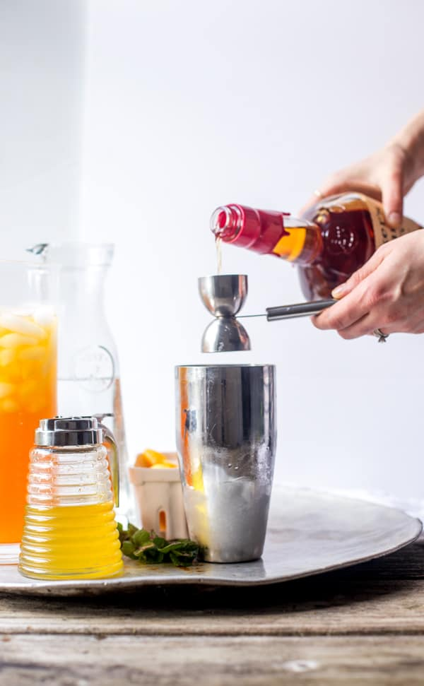 Maker's Mark® bourbon being poured into a stainless steel shaker with other ingredients around