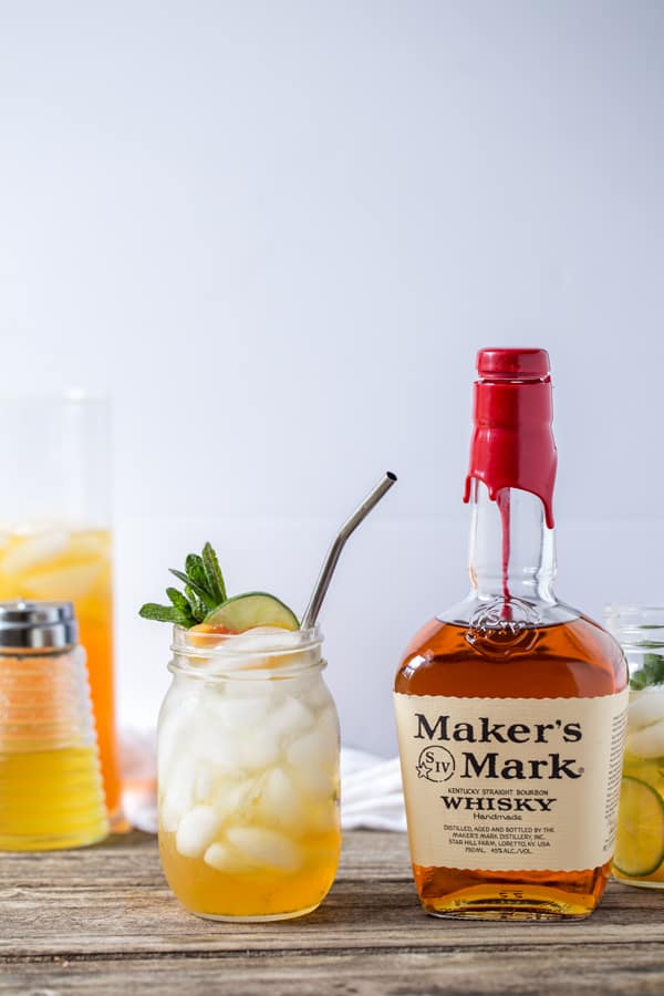 Maker's Mark bourbon, homemade ginger lime syrup in a vintage syrup canister and a batch of peach-infused black tea