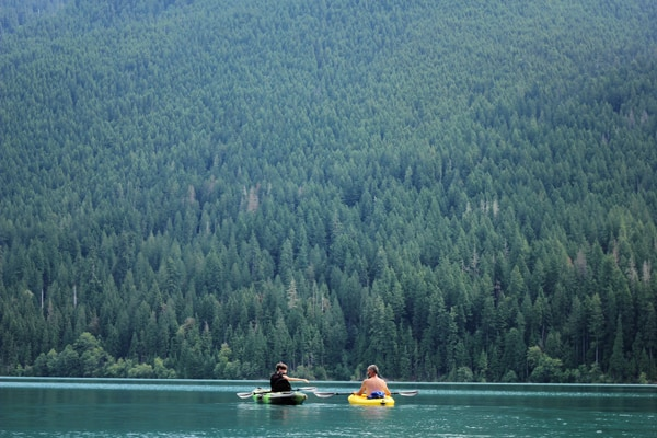 kayaking in a lake with evergreens in background