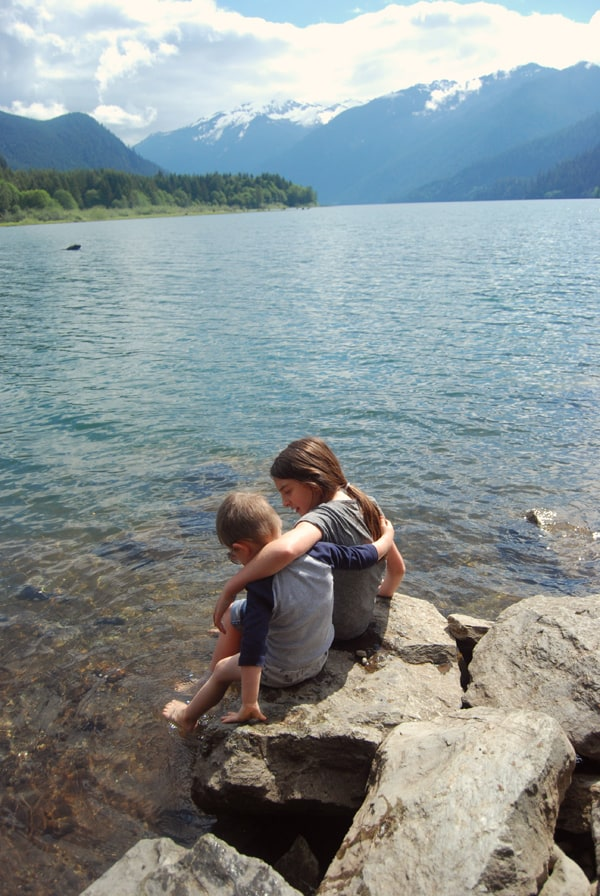 siblings at a lake with arms around each other