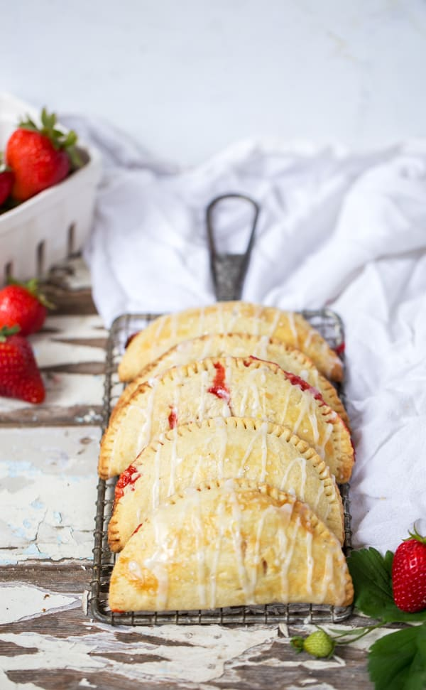 An easy two ingredient filling and a sturdy but flaky crust make these portable Strawberry Lemonade Hand Pies a hit at all your summer occasions! #strawberries #strawberrylemonade #handpies #strawberrypie How to Make Hand Pies | How to Freeze Hand Pies | Strawberry Hand Pies | Lemon Hand Pies | Lemon Pastry from ONEarmedMAMA.com