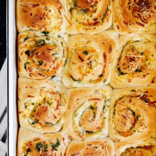 Roasted Garlic Cheese Buns are a savory take on the classic cinnamon roll. Stuffed with three cheeses, loads of garlic and fresh herbs these savory buns are great accompaniment to any meal!  #ad @BridgfordFood #bridgford, #bridgfordfoods #bridgfordkitchen #bakingwithbridgford cheese buns | Breakfast buns recipe | savory rolls | how to make garlic bread | easy cheese rolls recipe | roasted garlic bread  | make ahead freezer meals | breakfast | for a crowd  | garlic rolls | quick easy garlic rolls  | cheese stuffed buns | cheese buns in oven | cheese filling for buns  | garlic rolls with cheese inside | garlic rolls from frozen bread dough | garlic rolls with cream cheese