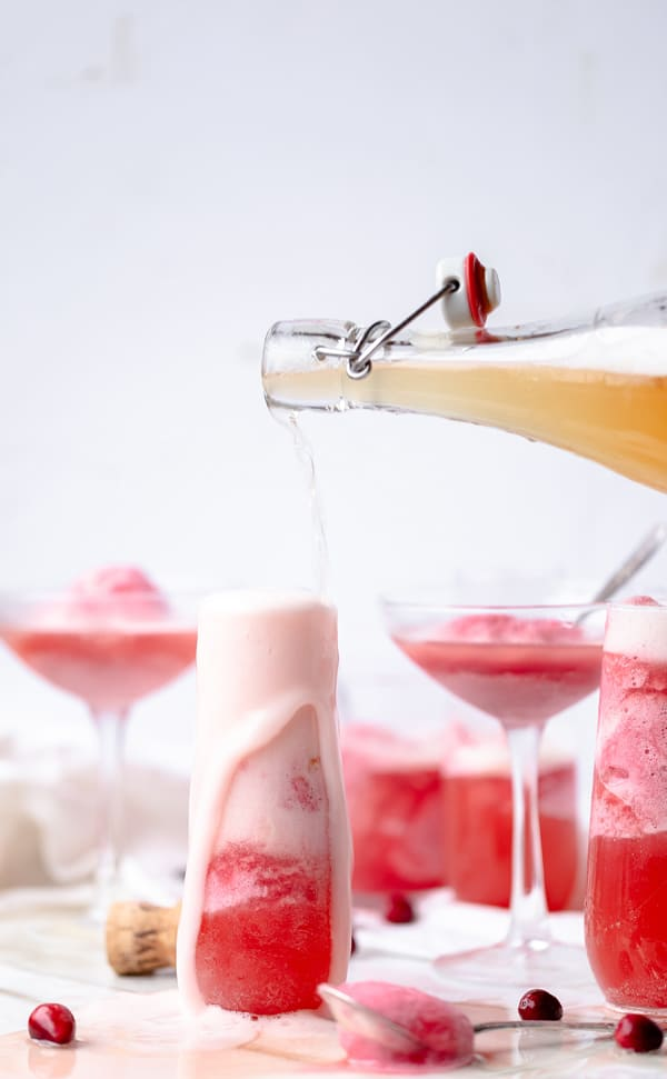 A champagne cocktail fitting for the season Cranberry Apple Mimosa Floats are a way to have your dessert and your after dinner drink in one! Cranberry Dessert Mimosa Cocktail for Fall , Thanksgiving and Christmas | homemade gluten free sorbet mimosa recipe | pink apple cider punch for a crowd | #cranberry #apple #sorbet #champagnecocktail