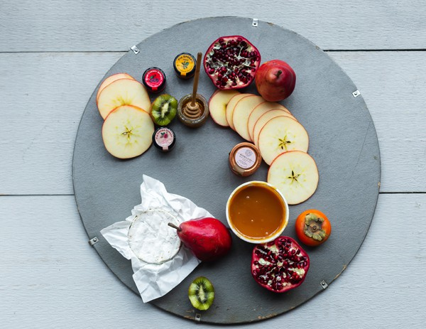 Start with the graphic items like round fruits and dips in containers with fixed shapes. Place them in a nice swooshing pattern then build off it for a natural look.
