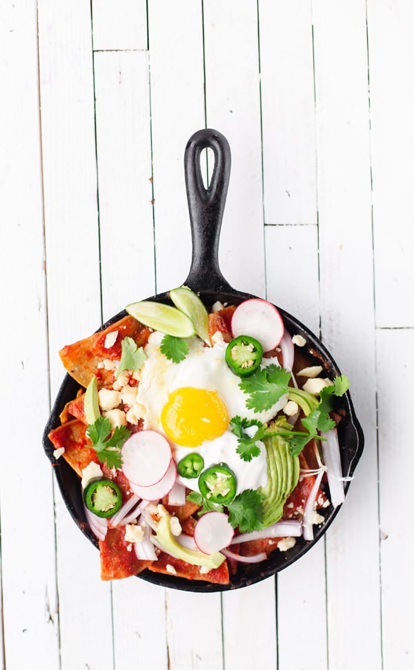 Easy Skillet Chilaquiles turn pantry staples like stale tortillas and canned tomatoes into a filling, fresh, and vibrant breakfast for one or for a crowd! How to make Easy Chilaquiles recipe with tomato sauce baked eggs   how to pronounce   rojos verdes breakfast gluten free vegetarian