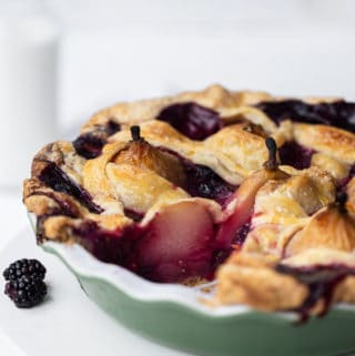 Pear Berry Pie is a stunning pear pie like none you've ever seen! Whole juicy pears and forest berries combine in a perfect, melt-in-your-mouth, all-butter pie crust. A drizzle of wildflower honey and a scoop of vanilla ice cream finishes this beautiful, upscale dessert. Flaky all butter pie crust recipe | poached pear pie recipe | pearberry | baked pear dessert #ad @PlugraButter