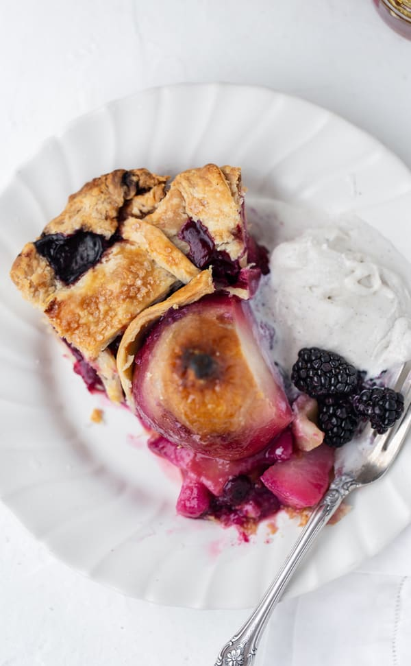Pear Berry Pie is a stunning pear pie like none you've ever seen! Whole juicy pears and forest berries combine in a perfect, melt-in-your-mouth, all-butter pie crust. A drizzle of wildflower honey and a scoop of vanilla ice cream finishes this beautiful, upscale dessert. Flaky all butter pie crust recipe   poached pear pie recipe   pearberry   baked pear dessert #ad @PlugraButter
