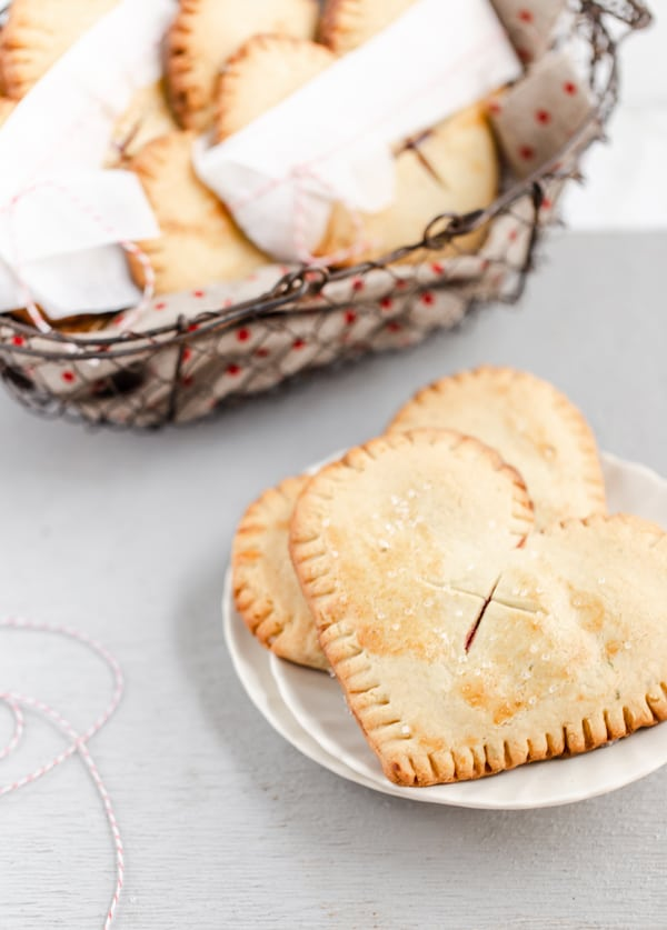 plate of flaky cherry pies and basket full of pies wrapped with parchment and bakers twine