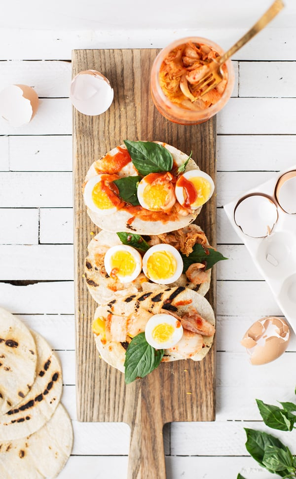 A quick, fueling breakfast Kimchi Egg Tacos combine perfectly cooked hard-boiled eggs with fresh basil and Korean kimchi and gochujang sauce | with gochujang corn tortillas | breakfast ideas | kimchi eggs recipes