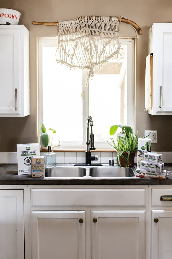 White kitchen with macrame window treatment and compostable k cups and compostable trash bags