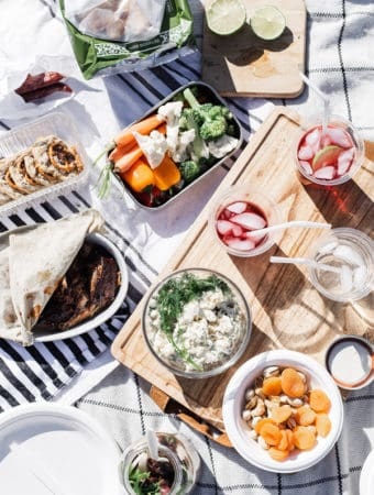 Overhead shot of a picnic flatlay with compostable straws, cups and plates