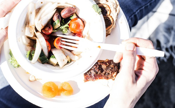 plate of bbq ribs, cold salads and beverages for a beach picnic with compostable plates, straws and cutlery