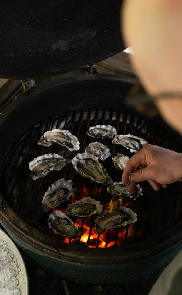 Overhead view of compound butter being put on charcoal smoked grilled oysters on the half shell