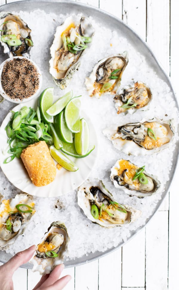 dozen oysters on a salt lined tray with a hand sneaking one off the bottom