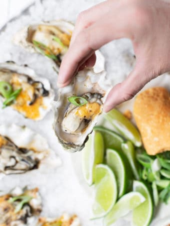 Overhead view of a hand holding a small oyster smoked and topped with miso butter scallions and togarashi