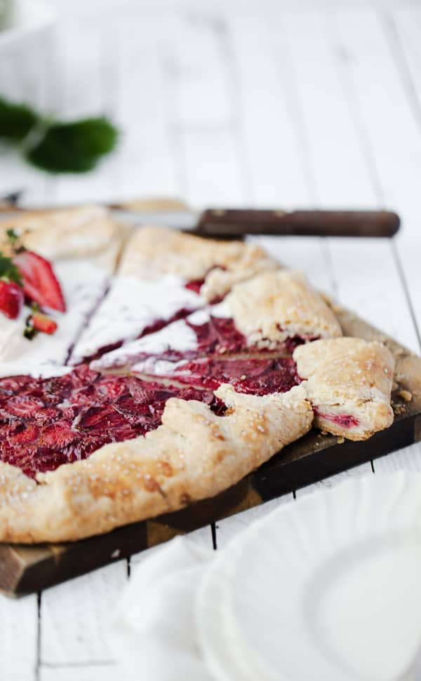 An easy -to-make impressive dessert with crisp pastry and jammy fruit filling Lemon Curd Wild Strawberry Galette is perfectly suited for summertime travel!  Strawberry galette | wild strawberry galette crostata recipe | rustic pie | galette dough pie crust recipe | strawberry recipes | lemon curd | strawberry lemon