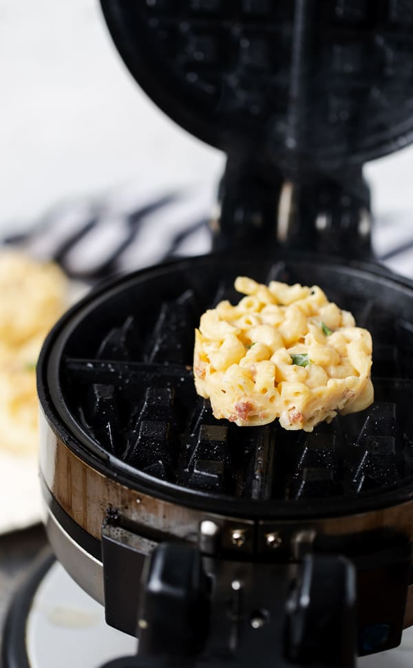Bacon Mac and Cheese Waffle Bites turns leftovers into crispy, golden brown mac and cheese that you can hold in your hand! With bacon, scallions and garlic, this homemade mac and cheese recipe is over-the-top flavorful! Bacon mac and cheese | best macaroni and cheese | waffle recipe | mac n cheese | waffle maker recipes | mac and cheese waffle #sponsored @smithfield