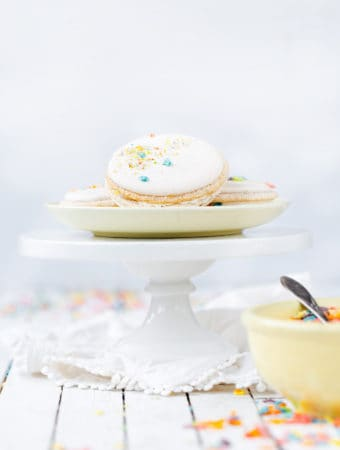 Fruity PEBBLES™ Cereal milk macarons stacked on cake stand with a vintage yellow cereal bowl. Bright white food photography #recipe #glutenfree #cookies #ad