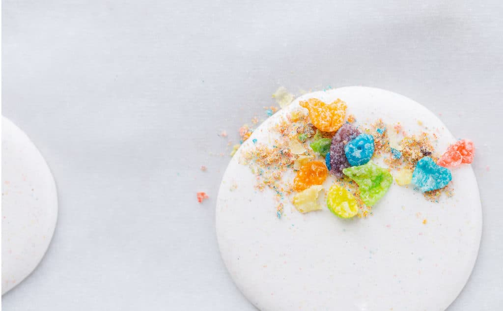 Cereal milk macaron shells topped with Fruity PEBBLES™ Cereal
