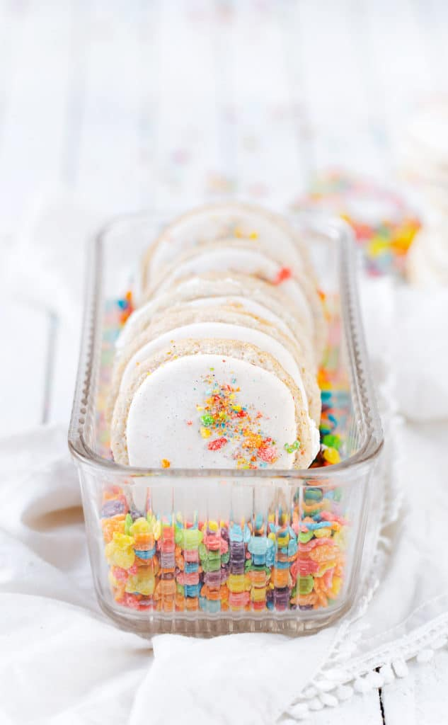A vintage glass refrigerator dish filled with Fruity PEBBLES™ #ad cereal milk macarons and Fruity PEBBLES™ Cereal minimal food photography