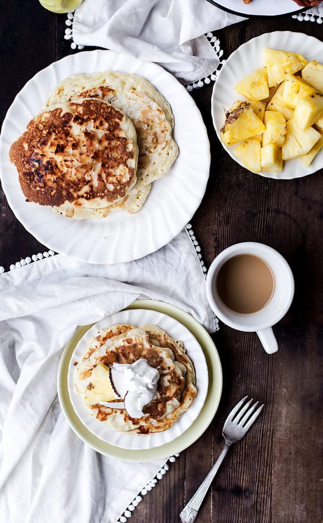 flatlay of breakfast table with bruleed pineapple coconut pancakes in center and plates along sides