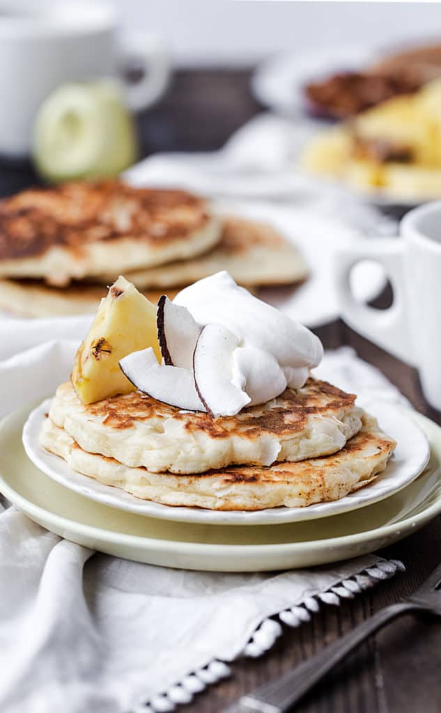 a brunch table with napkins, coffee cups, vintage creamer and pineapple pancakes