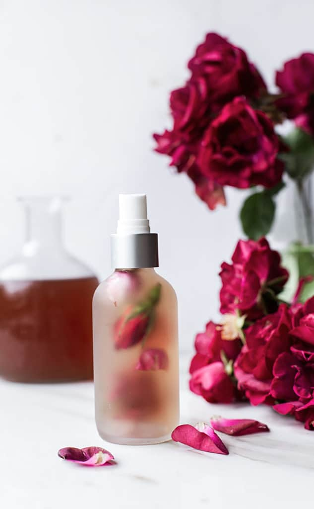 bottle of rose water with fresh roses and rose buds in the spray bottle