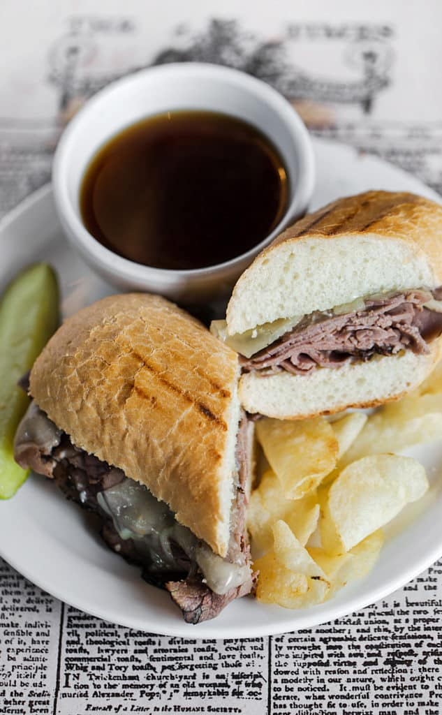Toasted beef dip sandwich on black and white paper