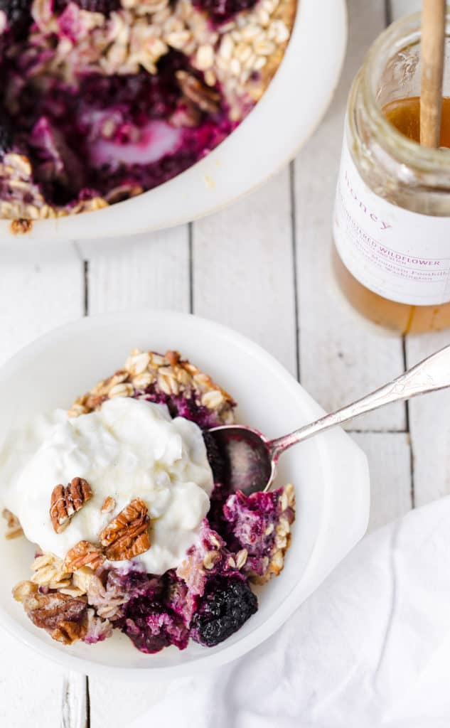 Scoop of blackberry baked oatmeal with greek yogurt and honey on the table