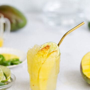 vibrant mango cocktail with a spicy mango spear in a cold glass