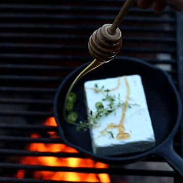 Swirl of honey being poured onto a skillet of roasted feta
