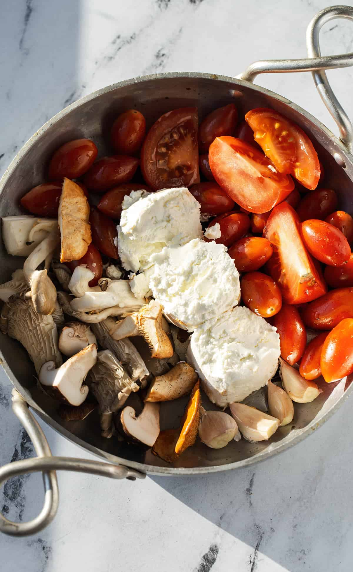 tomatoes mushrooms and goat cheese in skillet