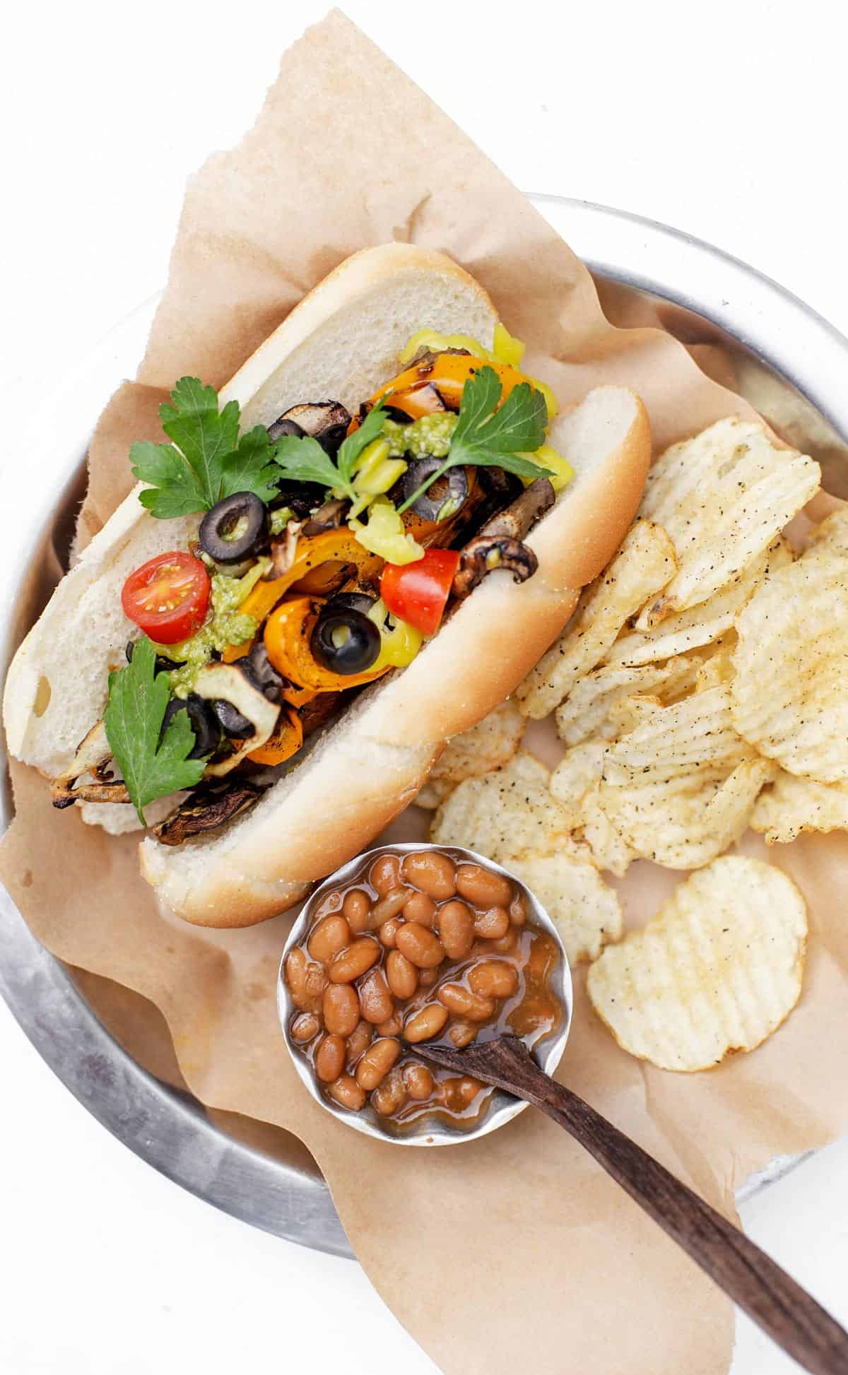 A gourmet hot dog recipe with grilled peppers, onions, parsley, pesto and more