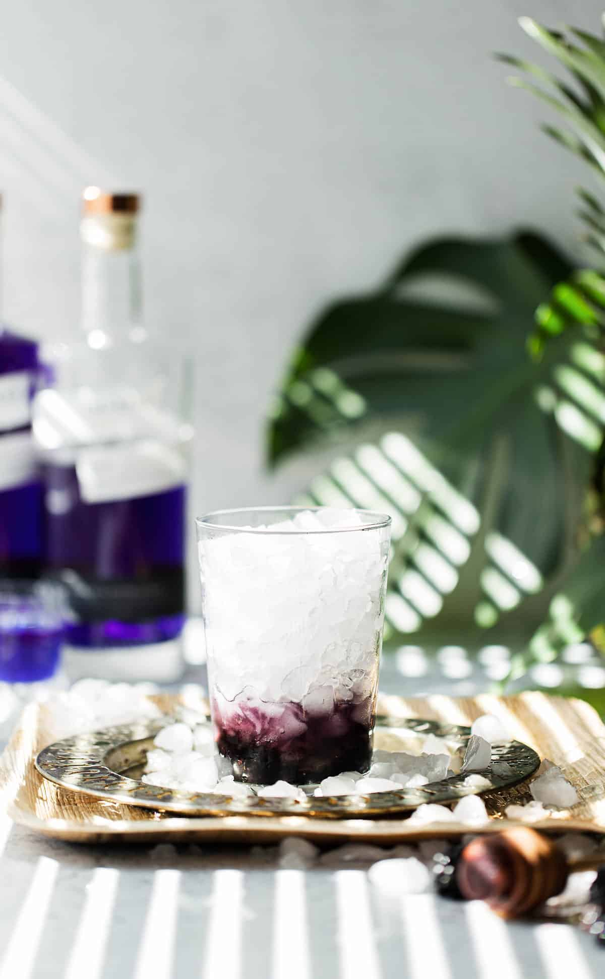 Muddled blackberries and honey in a glass with crushed ice
