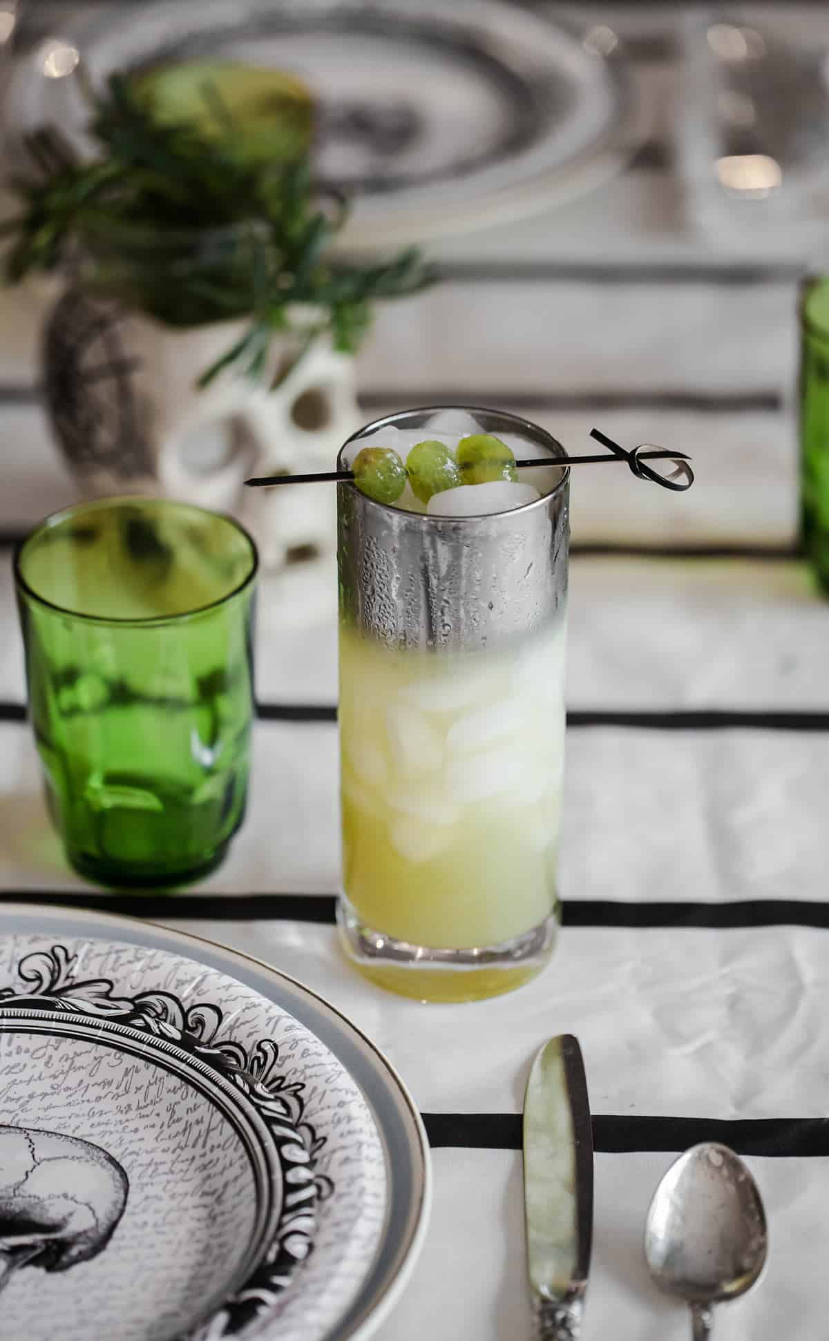 Green cocktail on a black white and green Halloween table